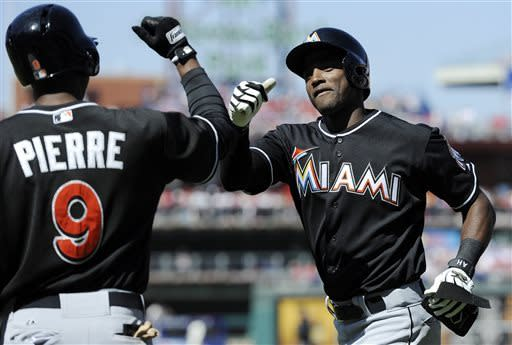 Miami Marlins' Adeiny Hechavarria, right, celebrates with Miami Marlins' Juan Pierre after hitting a grand slam in the third inning of an MLB National League baseball game on Sunday, May 5, 2013, in Philadelphia. (AP Photo/Michael Perez)