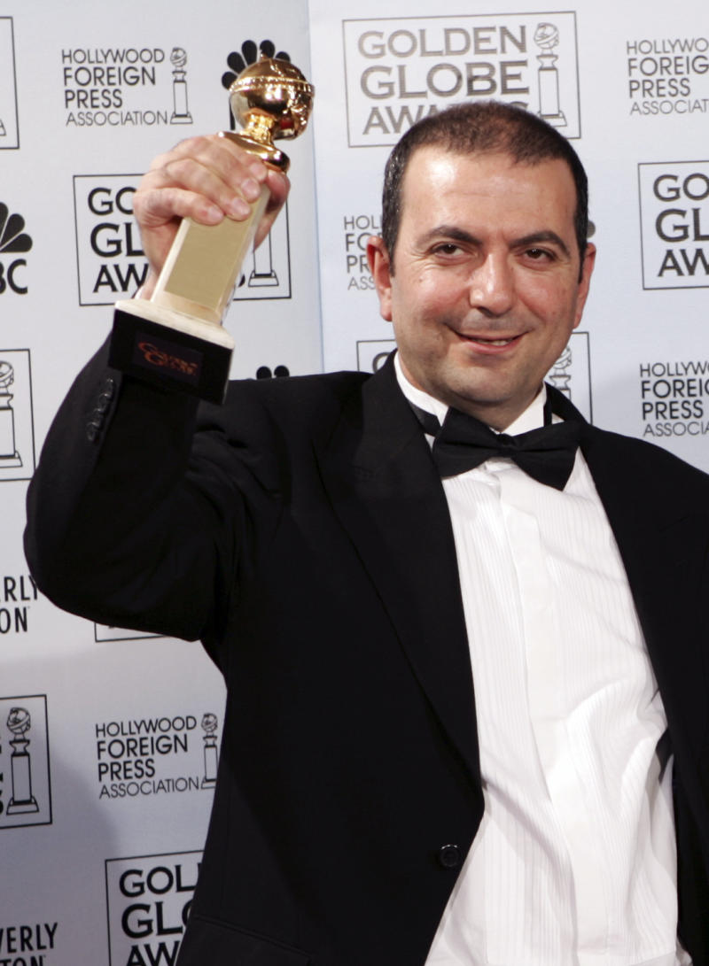 """FILE - This is a Monday, Jan. 16, 2006 file photo of  Hany Abu-Assad, writer/director of """"Paradise Now,"""" accepts the Golden Globe Award for Best Foreign Language film at the 63rd Annual Golden Globe Awards  in Beverly Hills, Calif. (AP Photo/Reed Saxon, File)"""
