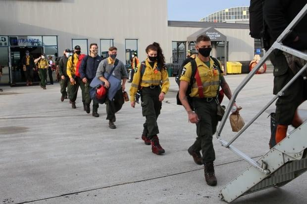 Wildland firefighters from Alberta board a plane bound for Ontario on Thursday. (Alberta Wildfire/Twitter - image credit)