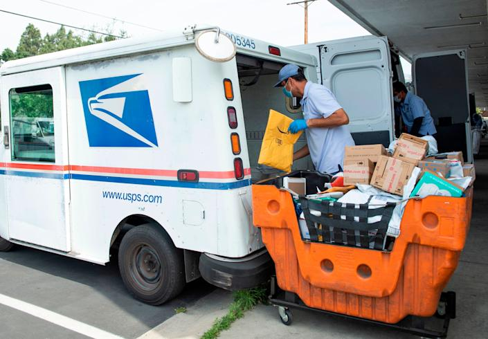 Mail carrier Oscar Osorio delivers mail and packages in the Los Feliz community of Los Angeles on April 29. (Photo: VALERIE MACON/AFP via Getty Images)