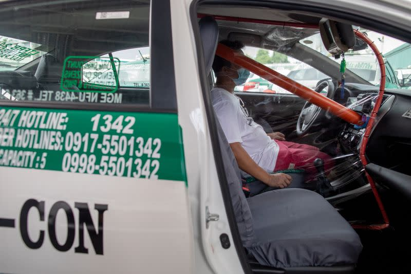 Taxis install makeshift barricades as lockdown eases in Manila