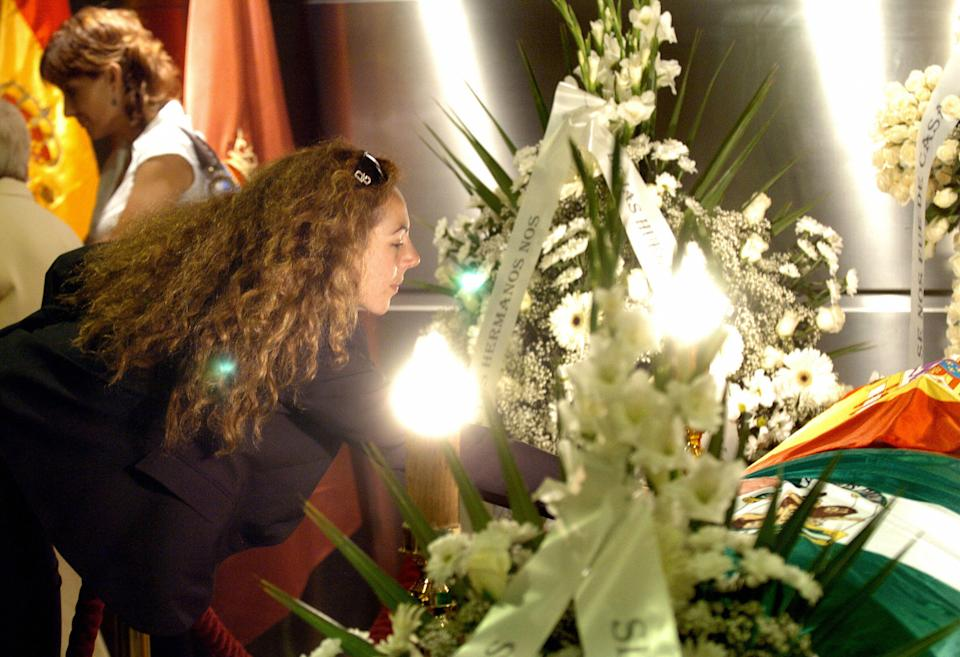 Madrid, SPAIN:  Rocio Carrasco (L), the daughter of Spanish singer Rocio Jurado touches her coffin in the temporary funeral chapel in the cultural centre in Plaza Colon, Madrid, 01 June 2006. Jurado, one of Spain's most beloved singers, died early Thursday after a long battle with pancreatic cancer. After a start in flamenco, Jurado later began singing in musical comedies and recording folk songs as well as appearing in films, earning a wide following in Spain and Latin America. AFP PHOTO/POOL/BALLESTEROS  (Photo credit should read BALLESTEROS/AFP via Getty Images)