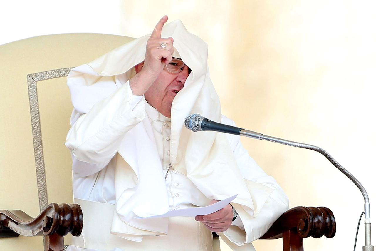<p>The robes of Pope Francis are blown over his head by a gust of wind as he delivers his homily during the weekly audience in St. Peter's Square on April 26, 2017, in Vatican City. Pope Francis will travel to Egypt to visit Cairo on April 28, 2017. (Photo: Franco Origlia/Getty Images) </p>