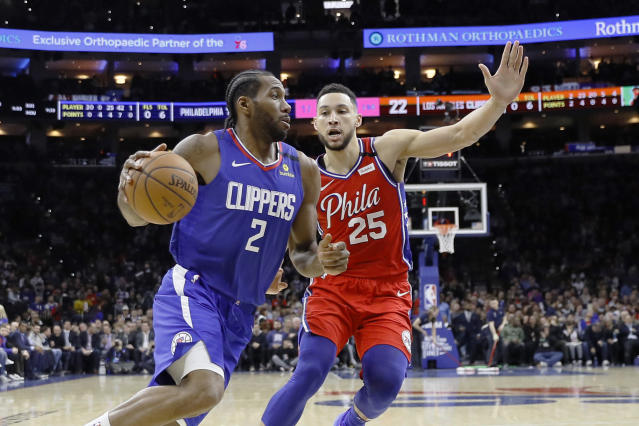 Los Angeles Clippers' Kawhi Leonard, left, drives past Philadelphia 76ers' Ben Simmons during the first half of an NBA basketball game, Tuesday, Feb. 11, 2020, in Philadelphia. (AP Photo/Matt Slocum)