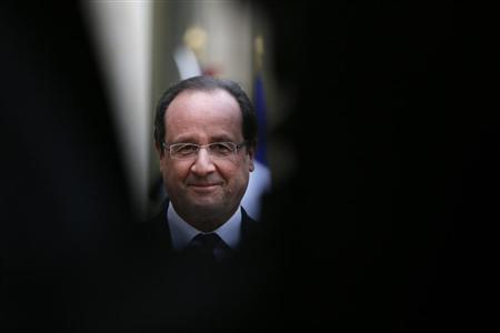 French President Francois Hollande talks to journalists in the courtyard of the Elysee Palace before a meeting in Paris