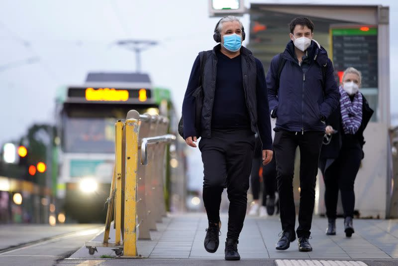 FILE PHOTO: People wear face masks in Melbourne, the first city in Australia to enforce mask-wearing to curb a resurgence of COVID-19