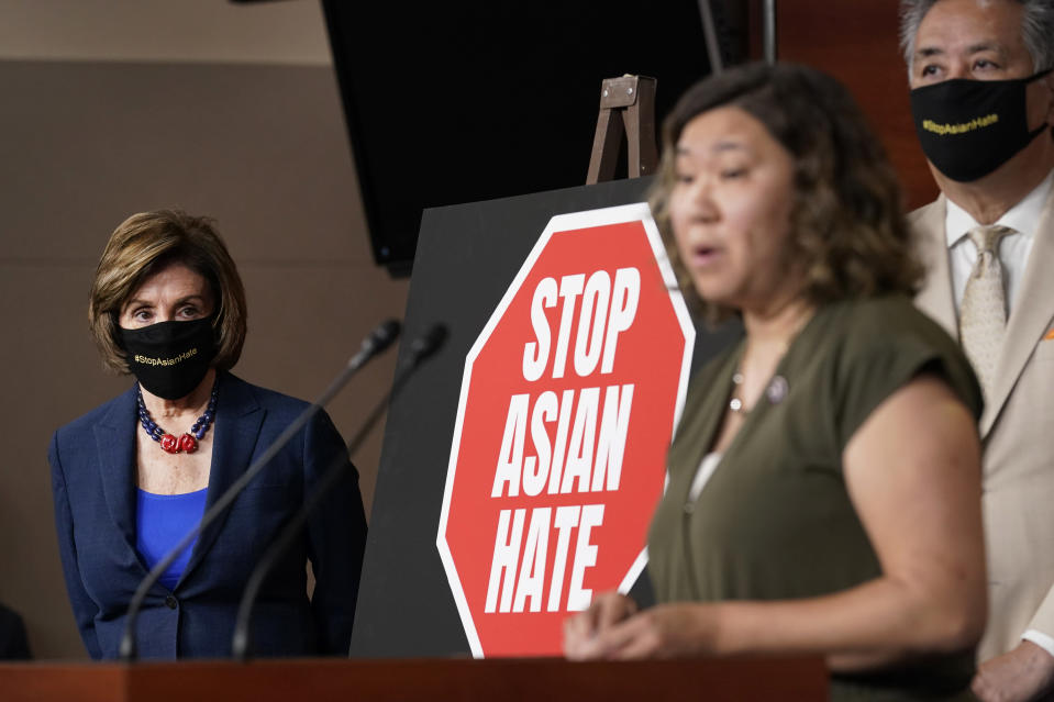 House Speaker Nancy Pelosi of Calif., left, listens as Rep. Grace Meng, D-N.Y., center, speaks during a news conference on Capitol Hill in Washington, Tuesday, May 18, 2021, on the COVID-19 Hate Crimes Act. Rep. Mark Takano, D-Calif., listens at right. (AP Photo/Susan Walsh)