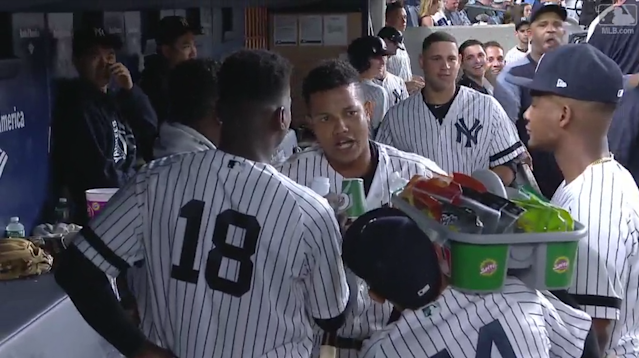 Starlin Castro is mock interviewed in the dugout by Yankees teammates Didi Gregorious and cameraman Ronald Torreyes. (MLB.com)