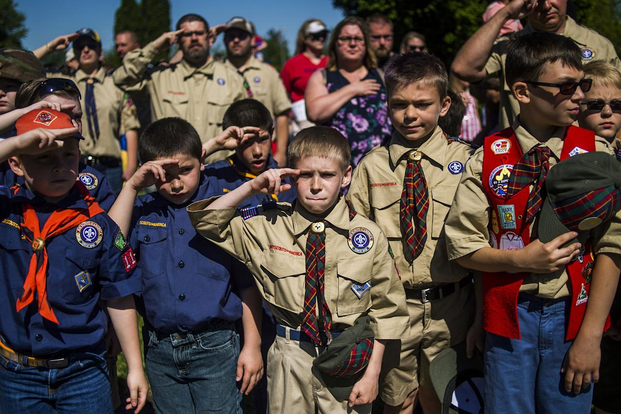 <p>Eli Whalen, 10, center, purses his lip as he salutes the lives of fallen soldiers who have made the ultimate sacrifice dying for their country in battle while paying his respects alongside fellow Boy Scouts and Cub Scouts alike on Memorial Day amidst hundreds of families attending a ceremony on Monday, May 29, 2017 at Fairview Cemetery in Linden, Mich. (Photo: Jake May /The Flint Journal-MLive.com via AP) </p>