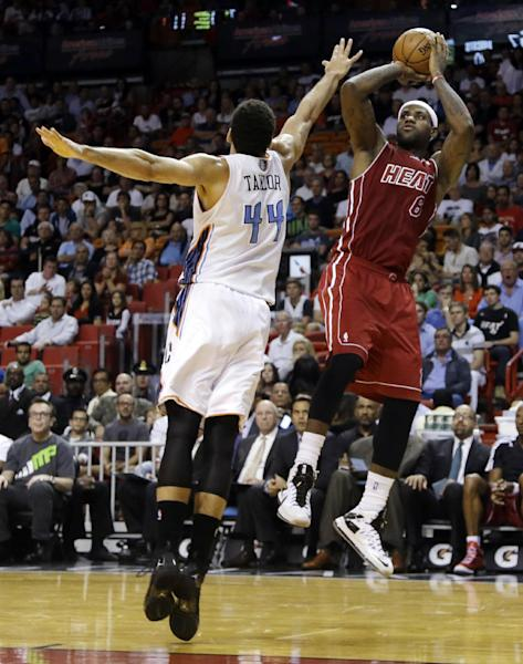 Miami Heat's LeBron James (6) shoots over Charlotte Bobcats' Jeff Taylor (44) during the first half of an NBA basketball game Sunday, Dec. 1, 2013, in Miami. (AP Photo/Lynne Sladky)