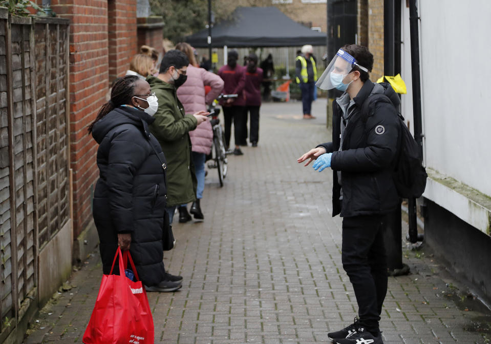 People queue for a COVID-19 test at a newly set-up testing facility in a car park in West Ealing, London, Tuesday, Feb. 2, 2021, after it emerged that the South African strain of the coronavirus may have started spreading in the local community. (AP Photo/Frank Augstein)