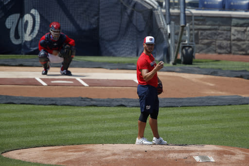 Washington Nationals' pitcher Tanner Rainey, foreground, pauses on the mound during a baseball training camp workout at Nationals Stadium, Sunday, July 5, 2020, in Washington. (AP Photo/Carolyn Kaster)