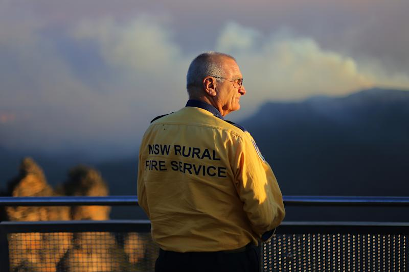 A NSW Rural Fire Service crew member looks out at the smoke-shrouded Three Sisters.