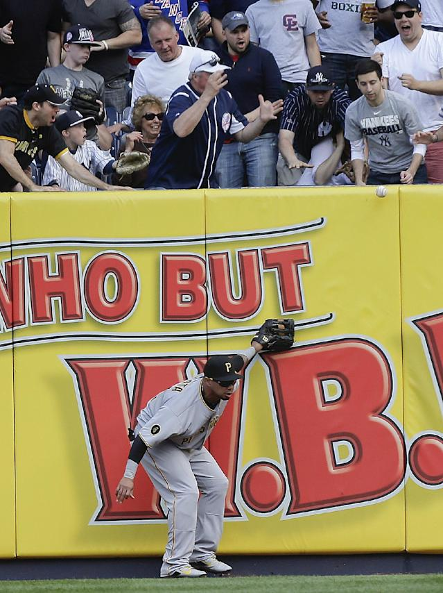 A home run ball hit by New York Yankees' Mark Teixeira bounces back onto the field after Pittsburgh Pirates right fielder Jose Tabata was unable to make the catch during the first inning of a baseball game, Saturday, May 17, 2014, in New York. Derek Jeter scored on the homer. (AP Photo/Julie Jacobson)