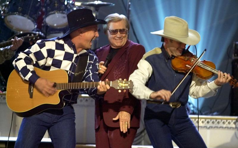 """FILE - In this Nov. 7, 2001 file photo, Garth Brooks, left, and George Jones, center, perform their duet """"Beer Run"""" at the Country Music Association Awards show in Nashville, Tenn.   The fiddle player at right is unidentified.   Jones, the peerless, hard-living country singer who recorded dozens of hits about good times and regrets and peaked with the heartbreaking classic """"He Stopped Loving Her Today,"""" has died. He was 81. Jones died Friday, April 26, 2013 at Vanderbilt University Medical Center in Nashville after being hospitalized with fever and irregular blood pressure, according to his publicist Kirt Webster.(AP Photo/M. Spencer Green, file)"""