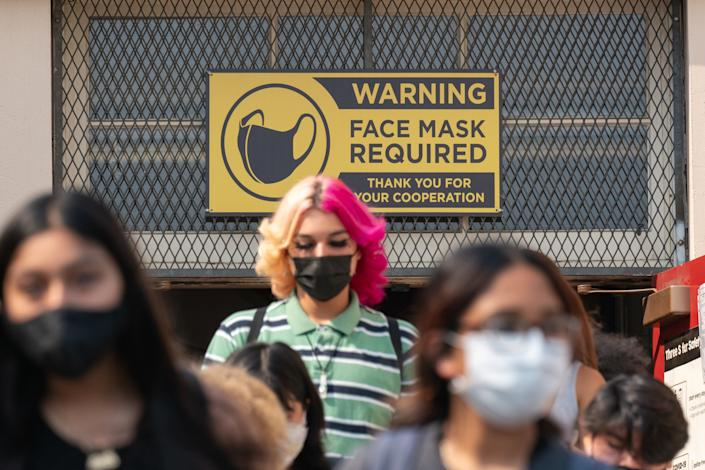 Students wearing face masks walk below a sign reading: Warning, face mask required. Thank you for your cooperation.