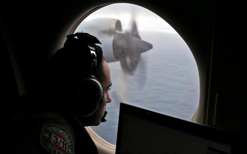 Flight officer Rayan Gharazeddine looks out of a Royal Australian Air Force (RAAF) AP-3C Orion as it flies over the southern Indian Ocean during the search for missing Malaysian Airlines flight MH370 March 22, 2014.  - Credit: Reuters