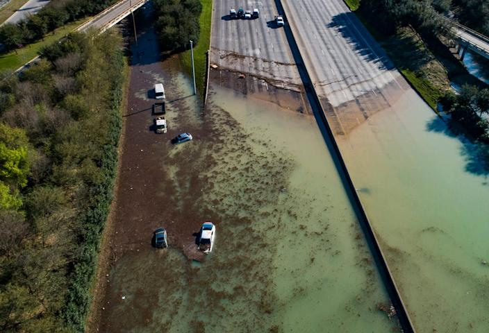 In this aerial photo, water is slowly draining from the freeway after a water main break east of the location flooded all lanes, closing the freeway in both directions, at the intersection of 610 and Clinton Drive in east Houston. Businesses and schools shut down after a main line from a plant that supplies water to about half of Houston burst open, submerging vehicles on the flooded freeway. Thursday, Feb. 27, 2020