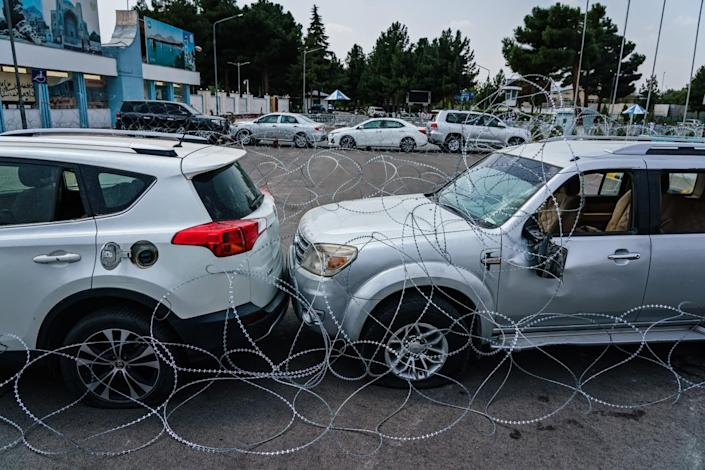 Barbed wire in front of two vehicles