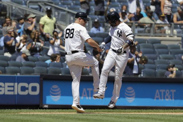 New York Yankees' Gleyber Torres, right, celebrates with third base coach Phil Nevin as he runs the bases after hitting a home run during the first inning of a baseball doubleheader against the Baltimore Orioles Monday, Aug. 12, 2019, in New York. (AP Photo/Frank Franklin II)