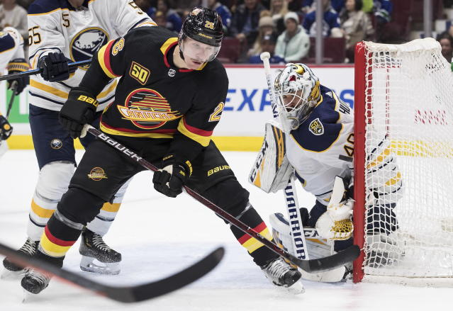Vancouver Canucks' Antoine Roussel, left, of France, watches the puck as it bounces off the post beside Buffalo Sabres goalie Carter Hutton during the second period of an NHL hockey game in Vancouver, British Columbia, Saturday, Dec. 7, 2019. (Darryl Dyck/The Canadian Press via AP)