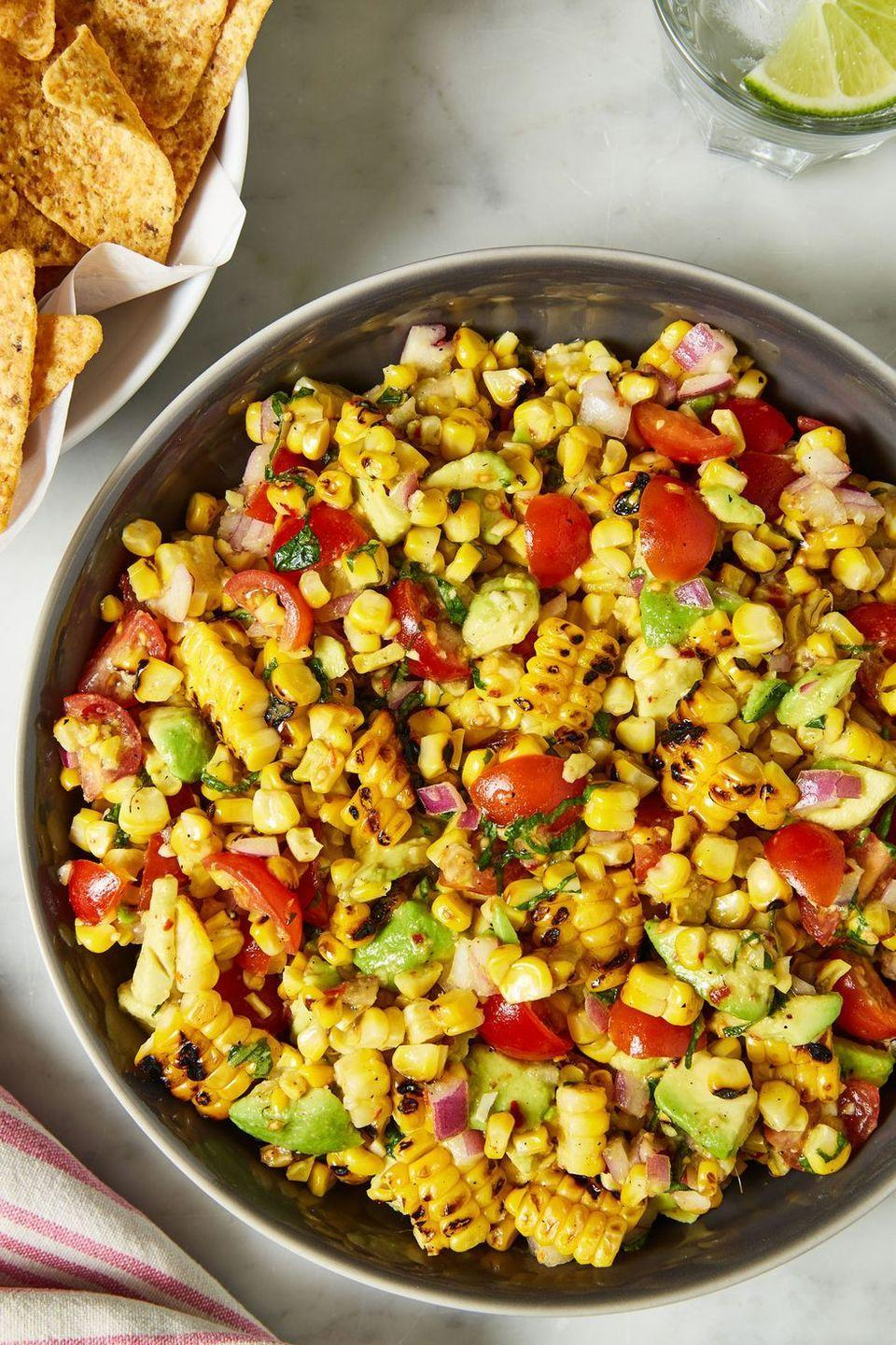 """<p>We love a good <a href=""""https://www.delish.com/uk/cooking/a32570797/easy-homemade-salsa-recipe/"""" rel=""""nofollow noopener"""" target=""""_blank"""" data-ylk=""""slk:Homemade Salsa"""" class=""""link rapid-noclick-resp"""">Homemade Salsa</a> in the summer. This one is especially good when sweet summer corn is in season. If you don't have a grill or grill pan, give your cobs a quick sear in a cast iron pan to get that smoky, charred flavour. You can also use frozen corn, (they even sell it pre-charred!) just make sure it's fully defrosted and drained of excess moisture before you make your salsa. </p><p>Get the <a href=""""https://www.delish.com/uk/cooking/recipes/a35346040/best-corn-salsa-recipe/"""" rel=""""nofollow noopener"""" target=""""_blank"""" data-ylk=""""slk:Grilled Corn Salsa"""" class=""""link rapid-noclick-resp"""">Grilled Corn Salsa</a> recipe.</p>"""