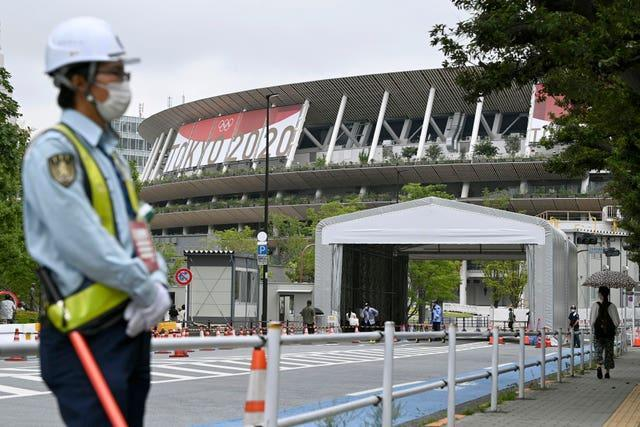 A security guard wearing a face mask guards the National Stadium in Tokyo