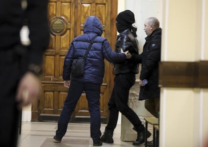 One of two terrorism suspects is escorted by the Federal Security Service (FSB), the main KGB successor agency, to a courtroom in St. Petersburg, Russia, Monday, Dec. 30, 2019. A court in St. Petersburg has ordered the detention of two Russian men who were arrested on a tip provided by the U.S. and are suspected of plotting unspecified terrorist attacks in the city during the New Year holidays. (David Frenkel/Kommersant Publishing House via AP)