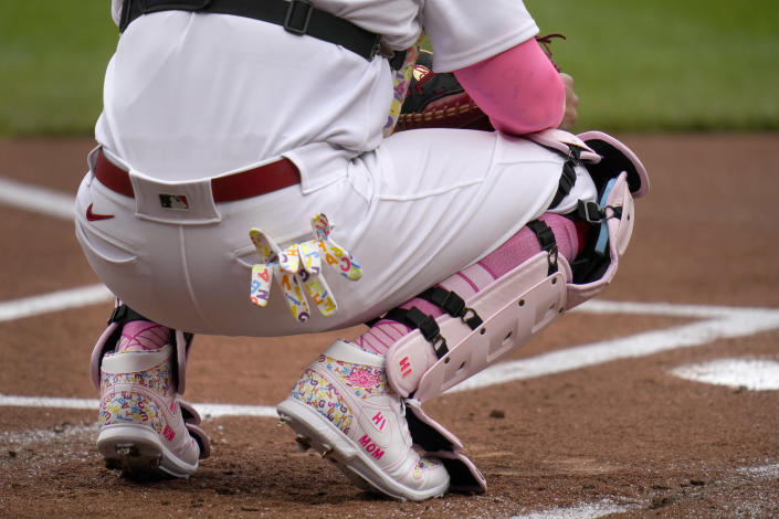 St. Louis Cardinals catcher Yadier Molina wears pink and a Mother's Day message on his shoe as he works behind the plate during the first inning of a baseball game against the Colorado Rockies Sunday, May 9, 2021, in St. Louis. (AP Photo/Jeff Roberson)
