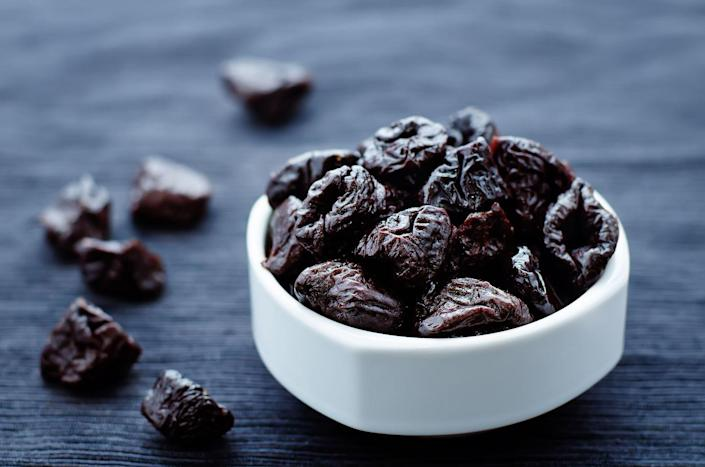"""<p>Dried prunes are notorious for helping with constipation, and with good reason. """"Prunes are a good source of fiber,"""" says Jessica Cording, M.S., R.D., author of <em><a href=""""https://www.amazon.com/Little-Book-Game-Changers-Managing/dp/163228068X?tag=syn-yahoo-20&ascsubtag=%5Bartid%7C10050.g.35715333%5Bsrc%7Cyahoo-us"""" rel=""""nofollow noopener"""" target=""""_blank"""" data-ylk=""""slk:The Little Book of Game-Changers"""" class=""""link rapid-noclick-resp"""">The Little Book of Game-Changers</a></em>. Prunes also contain a compound called sorbitol that helps soften poop and makes it easier to pass through your system, she says. Want to get even more bang from your prunes? Dr. Farhadi recommends soaking them in water overnight.</p>"""