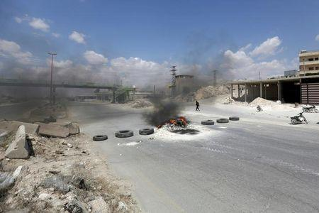 File photo of an armed gunman walking near burning tyres as protesters block Damascus-Aleppo highway in the rebel-controlled area of Maaret al-Numan town in Idlib province