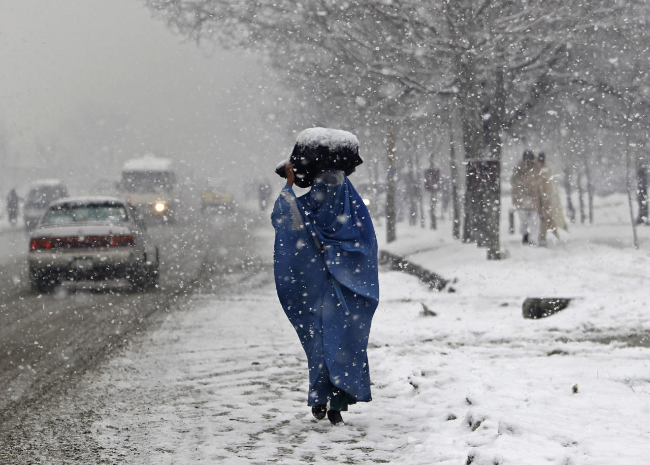 A woman carries a sack on her head along a street on a snowy day in Kabul February 11, 2012.  REUTERS/Omar Sobhani (AFGHANISTAN - Tags: SOCIETY TPX IMAGES OF THE DAY ENVIRONMENT)