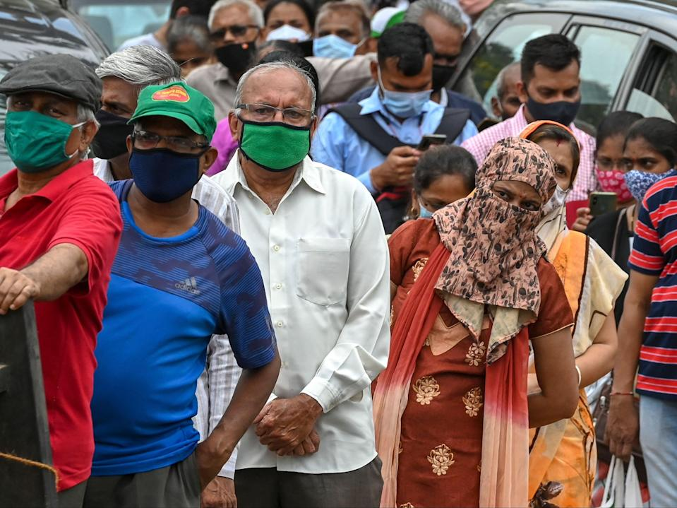 People wait in a queue to receive the Covid-19 coronavirus vaccine at a vaccination centre in Mumbai (PUNIT PARANJPE/AFP via Getty Images)