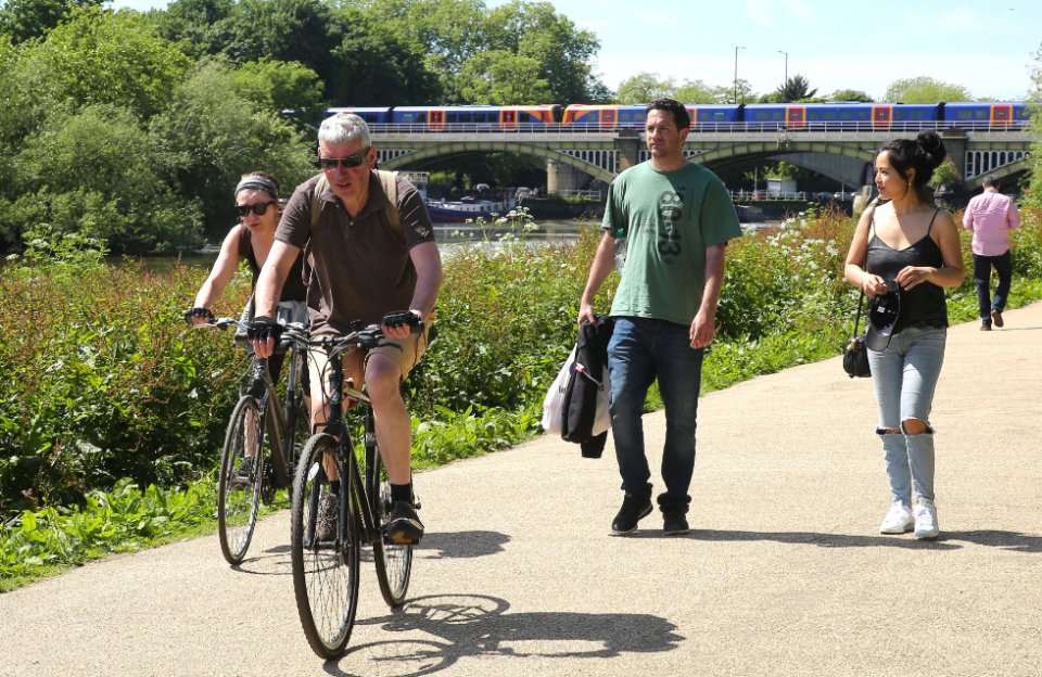 <p>Cyclists in Richmond are seen pedalling in the heat (Picture: REX) </p>