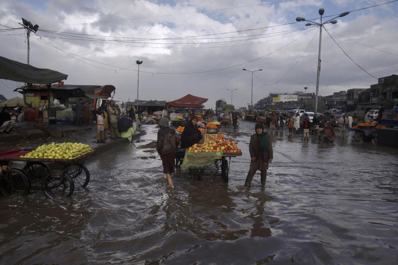 Pakistani boys selling fruit stand next to their stalls in a flooded street following heavy rain, in a market on the outskirts of Islamabad, Pakistan, Monday, Feb. 7, 2011. (AP Photo/Muhammed Muheisen)