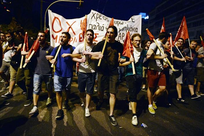 Protesters march, holding banners and flags in front of the Greek parliament in Athens during an anti-austerity protest on July 15, 2015 (AFP Photo/Louisa Gouliamaki)