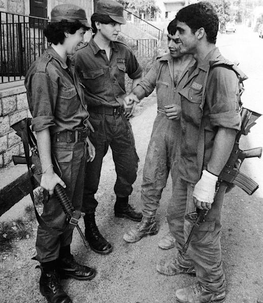 FILE - In this Aug. 3, 1982 file photo, two female Phalangist soldiers, Lebanese Christian Militia, talking with two Israeli soldiers at a street in Jounieh, east Beirut, Lebanon. The Lebanese civil war itself played out in several stages between 1975 and 1990. Over that time, Christians fought Palestinians, Lebanese Sunni and Shiite Muslims and Druse. At one point, Christian groups turned their guns on each other, in a nasty episode of fratricidal bloodshed later repeated by Shiite militias. (AP Photo/Maz Nash, File)