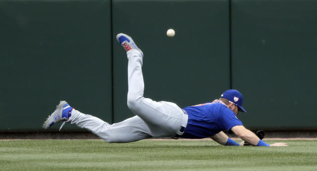 Chicago Cubs center fielder Ian Happ tumbles to the turf after diving for, and missing, a fly ball that fell in for a two-run double by Oakland Athletics' Khris Davis in the third inning of a spring training baseball game, Wednesday, March 13, 2019, in Mesa, Ariz. (AP Photo/Elaine Thompson)