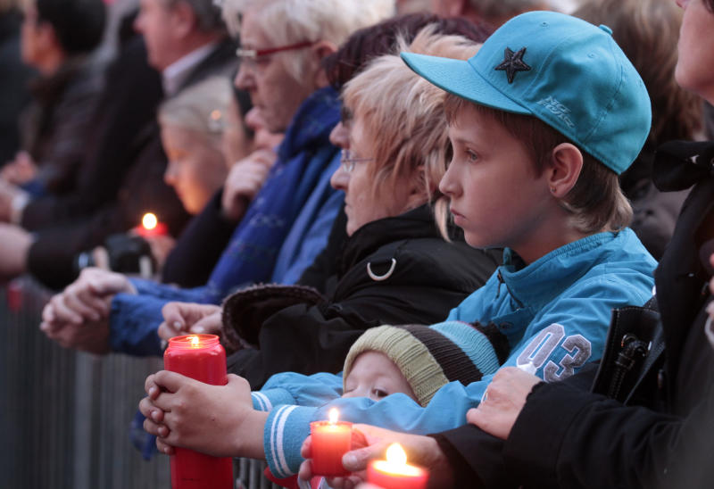 A boy holds a candle as he attends a vigil in between the town hall and the Saint Peters church in Leuven, Belgium, Wednesday, March 21, 2012. Mourners attended a vigil for victims of last week's bus crash in a Swiss tunnel that killed 22 children and six adults. (AP Photo/Yves Logghe)