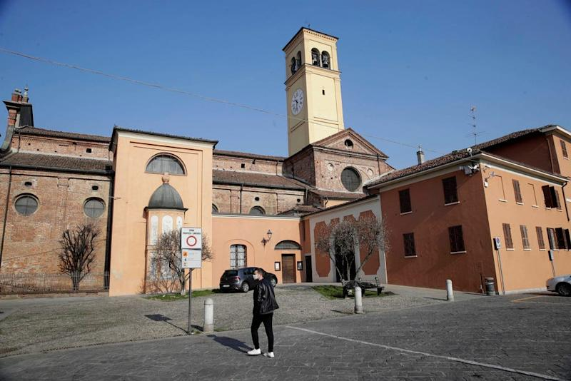 A man walks past the San Biagio church in Codogno in northern Italy on Saturday.