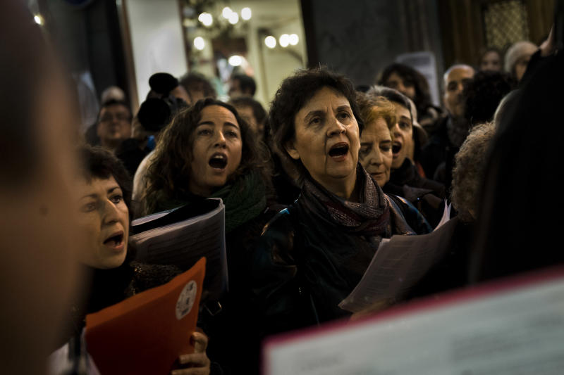People sing while they take part in a protest against evictions in front of a Bankia bank in Madrid, Friday, Nov. 9, 2012. A woman in Spain jumped to her death from her balcony in a suburb of the northern Spanish city of Bilbao as bailiffs approached to evict her from her fourth-floor apartment for failing to pay the mortgage. It was the second apparent suicide linked to evictions, and it further illustrates the dire conditions many Spaniards find themselves in as the country's economy sinks. (AP Photo/Daniel Ochoa de Olza)
