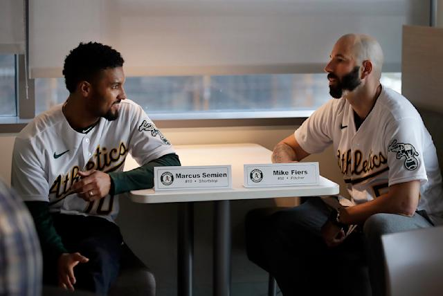 Oakland Athletics pitcher Mike Fiers, right, speaks with shortstop Marcus Semien prior to an interview with the media on Friday, Jan. 24, 2020, in Oakland, Calif. Fiers, the Oakland pitcher and whistleblower in the Houston Astros sign-stealing scandal, appeared with teammates and manager Bob Melvin at team offices. Fiers has not spoken publicly about the sign stealing since the story was published in The Athletic in November. (AP Photo/Ben Margot)