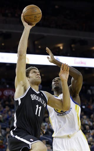 Brooklyn Nets' Brook Lopez (11) shoots next to Golden State Warriors' Festus Ezeli (31) during the first half of an NBA basketball game in Oakland, Calif., Wednesday, Nov. 21, 2012. (AP Photo/Marcio Jose Sanchez)