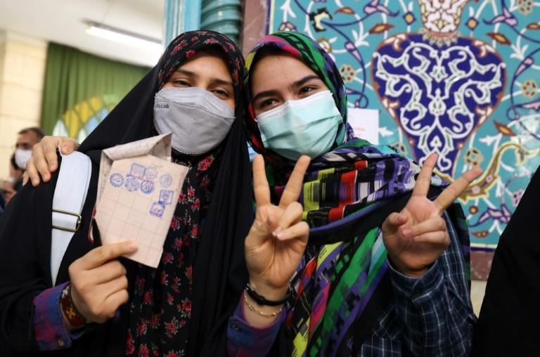 Iranian women pose for a picture during voting at a polling station in Tehran