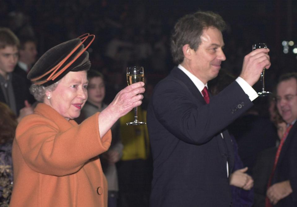 <p>Queen Elizabeth II and Prime Minister Tony Blair raise their glasses as midnight strikes during the Opening Celebrations at the Millennium Dome in Greenwich, London. (PA) </p>