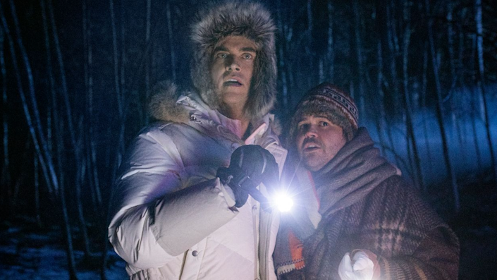 Two men dressed in winter coats look scared in the woods.