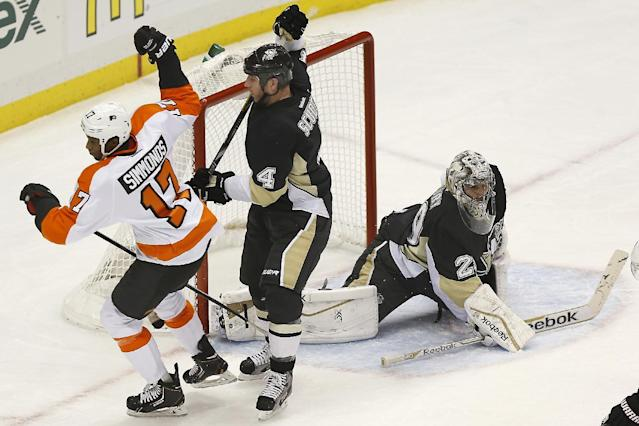 Philadelphia Flyers' Wayne Simmonds (17) celebrates past Pittsburgh Penguins' Rob Scuderi (4) after scoring on goalie Marc-Andre Fleury, right, during the first period of an NHL hockey game on Sunday, March 16, 2014, in Pittsburgh. (AP Photo/Keith Srakocic)