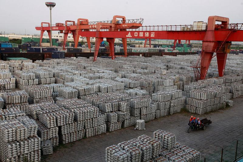 FILE PHOTO: Workers ride on an motor rickshaw through an aluminium ingots depot in Wuxi
