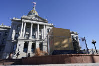 Fencing stands around the base where a Civil War monument once stood outside the west steps of Colorado's State Capitol as security measures are put in place to protect against any breaches during weekend protests planned outside the building Friday, Jan. 15, 2021, in Denver. With the FBI warning of potential violence at all state capitols Sunday, Jan. 17, the ornate halls of government and symbols of democracy looked more like heavily guarded U.S. embassies in war-torn countries. (AP Photo/David Zalubowski)