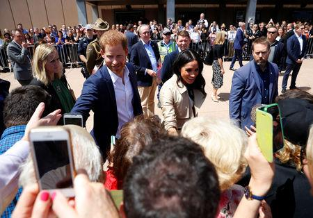 People take photos of Britain's Prince Harry and wife Meghan, Duchess of Sussex during a visit at the Sydney Opera House in Sydney, Australia October 16, 2018. REUTERS/Phil Noble